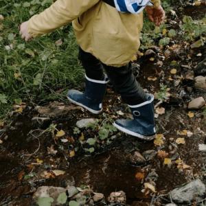 Kind mit gelber Jacke und Stiefeln im Flussbett