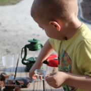 Kind mit Lupe im Rahmen der Umweltbildung